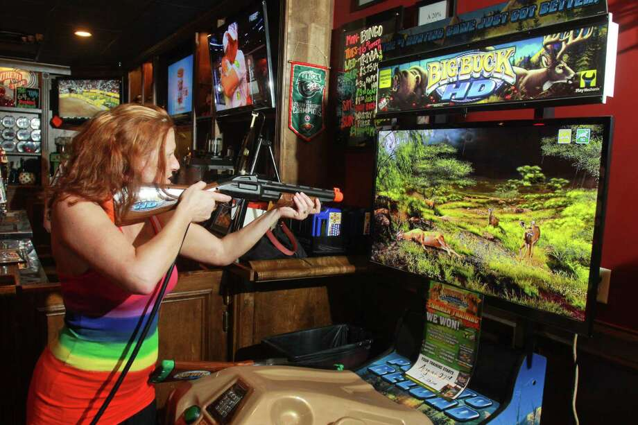 Kelly Folly says she is very competitive when it comes to playing Big Buck Hunter. She's ranked 14th in the world on the arcade game. Photo: Gary Fountain, Freelance / Copyright 2013 Gary Fountain.