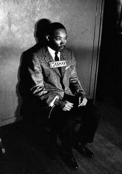 Rev. Martin Luther King Jr., director of segregated bus boycott, with 7080 sign across his chest for police mug shot, sitting on chair against wall in station house after his arrest for directing city-wide boycott of segregated buses in 1956. Photo: Don Cravens, Time & Life Pictures/Getty Image / Don Cravens
