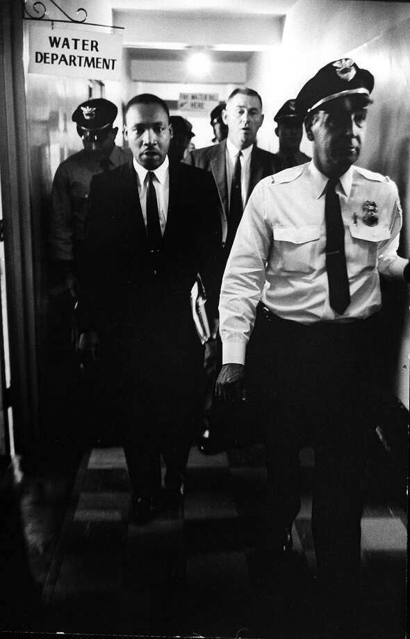 Civil Rights leader Rev. Martin Luther King Jr. escorted by police officers in courthouse as he is taken into a hearing on a charge of probation violation following his arrest for assisting a student sit-in demonstration. Photo: Donald Uhrbrock, Time & Life Pictures/Getty Image / Donald Uhrbrock