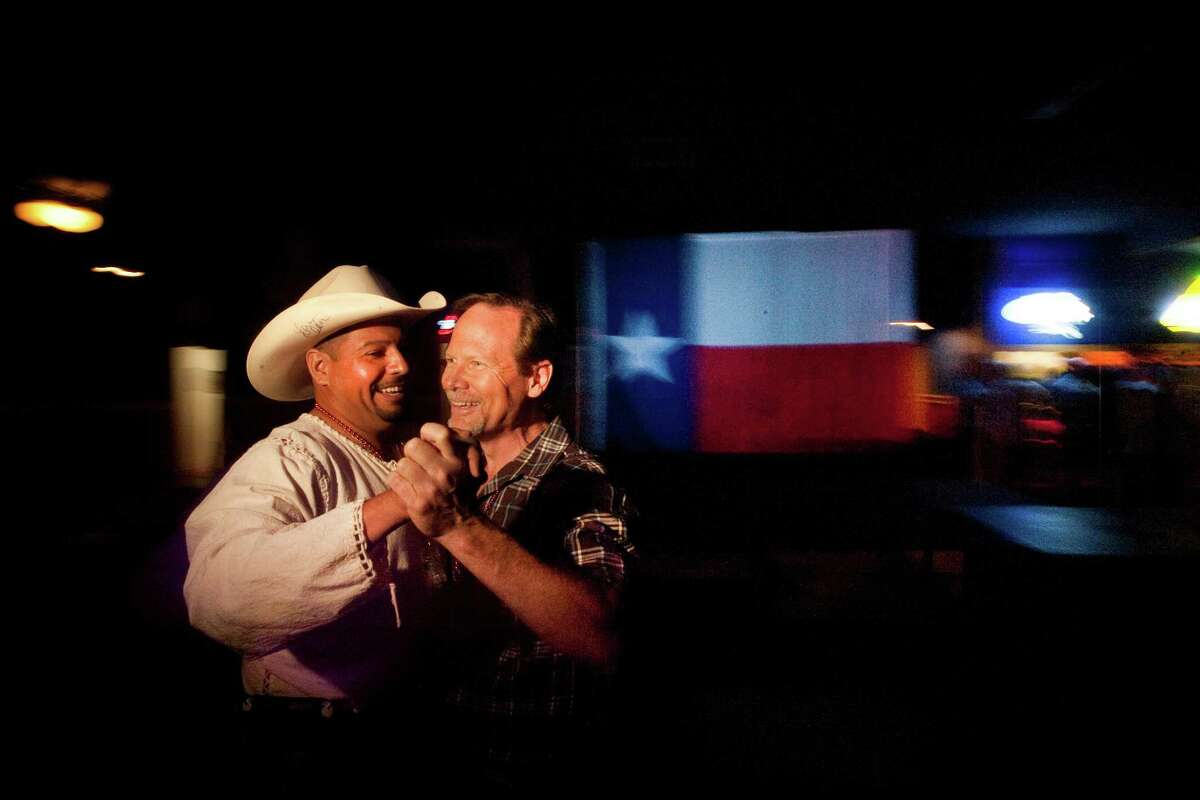 """Jesse Vargas and Doug Paulsen dance at the Neon Boots Dancehall and Saloon, a country-style gay, lesbian and transgender bar located in the former home of the Esquire Ballroom at 11410 Hempstead Highway Thursday, Aug. 15, 2013, in Houston. The Esquire has gone through many transitions. It began as a plaice where Willie Nelson played a regular gig and wrote the song """"Night Life"""" about the place. Patsy Cline used to sing there too. The hall eventually evolved into Latin dance clubs and now has gone back to its country roots. ( Johnny Hanson / Houston Chronicle )"""