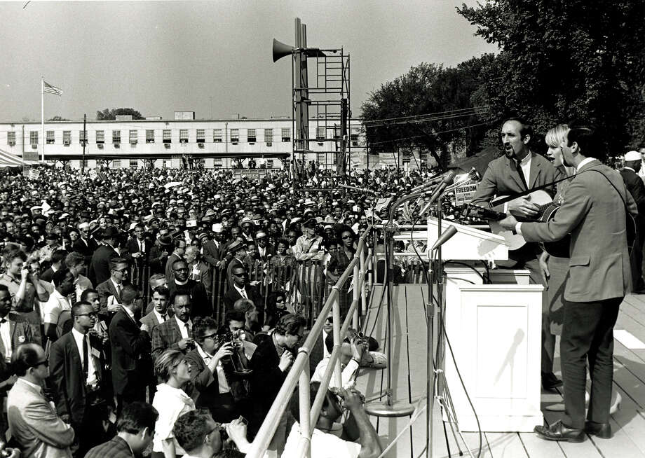 American folk and pop group Peter, Paul and Mary perform during the March on Washington for Jobs and Freedom, Washington DC, August 28, 1963. The trio behind the microphone features, from left, Paul Stookey, Mary Travers (1936 - 2009), and Peter Yarrow. The march and rally provided the setting for the Rev. Martin Luther King Jr.'s iconic 'I Have a Dream' speech. Photo: PhotoQuest, Getty Images / Archive Photos