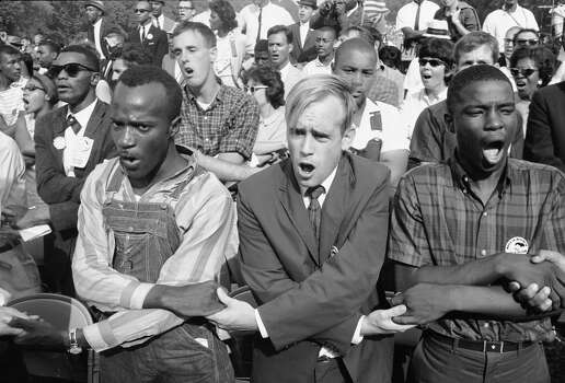 View of people as they hold hands and sing during the March on Washington for Jobs and Freedom, Washington DC, August 23, 1963. The march provided the setting for Rev. Marin Luther King Jr.'s iconic 'I Have a Dream' speech. Photo: Paul Schutzer, Time & Life Pictures/Getty Image / Time & Life Pictures