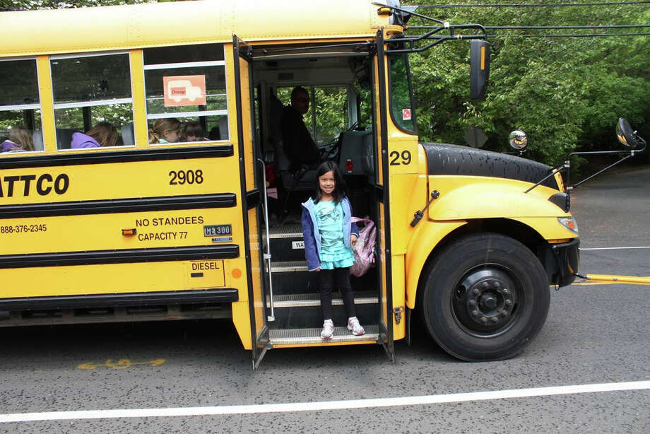 Katie Tsang, whose parents Norman and Betty Tsang developed an app to help Westport students and parents track the location of their school bus, exits her bus on on a trip home last spring. Photo: Contributed Photo / Westport News