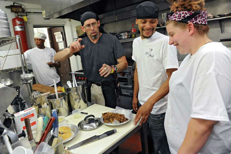 Chef and general manager Chick Hawksley, second from left, trains staff member Carl Pierce of Albany, left, Alfonzo Hill of Albany and Janelle Anzinao of Albany, right, Friday, Aug. 16, 2013, in the kitchen at Jugs & Mugs on Madison Ave., in Albany, N.Y. The staff was training and menu sampling for new restaurant. (Lori Van Buren / Times Union) Photo: Lori Van Buren / 00023538A