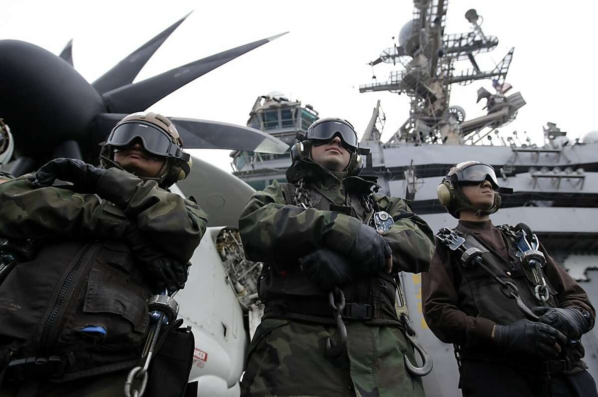 A picture taken Monday, Feb. 13, 2012 shows, plane captains stand by to receive an aircraft on the flight deck of the Nimitz-class aircraft carrier USS Abraham Lincoln (CVN 72) during fly exercises in the Persian Gulf. The Carrier sailed from the Persian Gulf through the Strait of Hormuz on Tuesday. (AP Photo/Hassan Ammar)