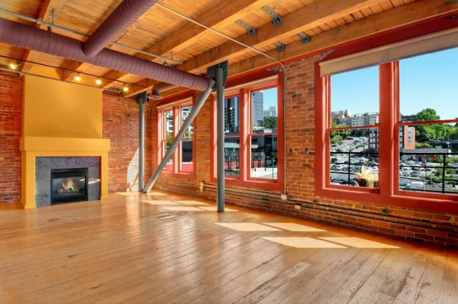 Moving over to Pioneer Square, here's 210 3rd Ave. S., unit 5d. The 2,624-square-foot home, in a 1904 building, has two bedrooms, 2.25 bathrooms, two fireplaces, brick walls, vaulted, wood-beamed ceilings, four skylights, two parking spaces and views of Downtown Seattle and the sports stadiums. It's listed for $1.15 million. Photo: Courtesy Jeff J. Reynolds, Windermere Real Estate