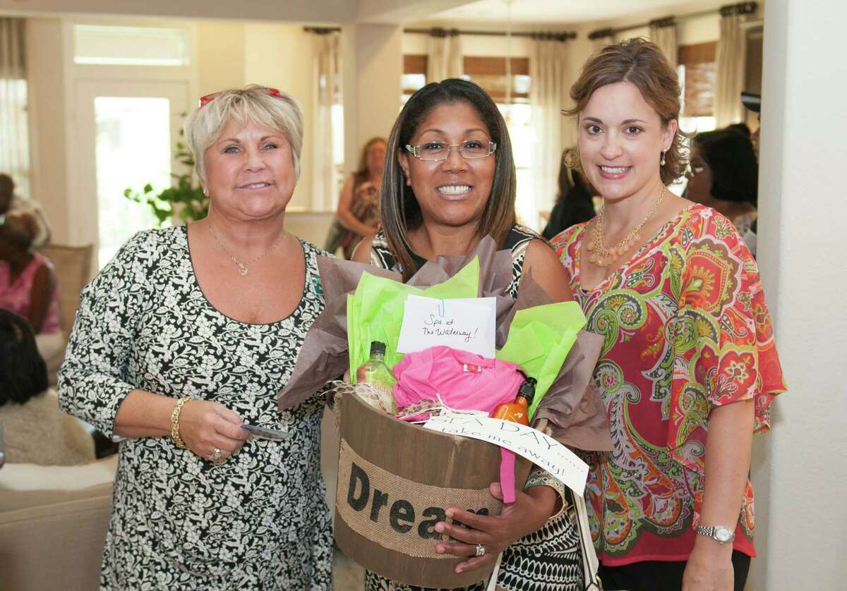 Christina Smith-Simmons of Realty Associates, center, won a spa treatment basket from Becca Phillips, left, sales counselor of Highland Homes and Kristi Steward, director of marketing for Harmony, a project of The Johnson Development Corp.