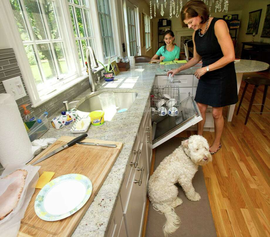 Nancy Nessel does dishes as her daughter, Amanda, 10, works on homework and the family dog, Oakley, sits nearby in their Darien home on Tuesday, August 20, 2013. Photo: Lindsay Perry / Stamford Advocate