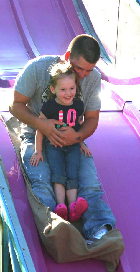 Kamryn Burns, 3, and her dad, Eddie Burns, of New Milford ride tandem down the slide, one of the many carnival rides at the 62nd Bridgewater Country Fair, Aug. 16-18, 2013 in Bridgewater. Photo: Deborah Rose