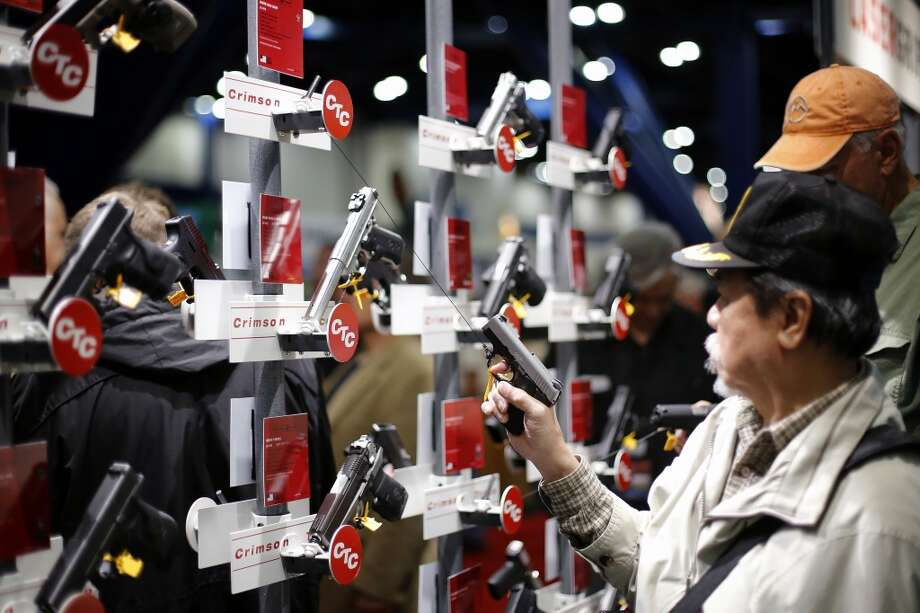 An expo attendee inspects a pistol, during day 2 of the 142nd NRA annual meetings and exhibits, Saturday, May 4, 2013 at the George R Brown convention center in Houston, Texas. (TODD SPOTH FOR THE CHRONICLE) Photo: © TODD SPOTH, 2013
