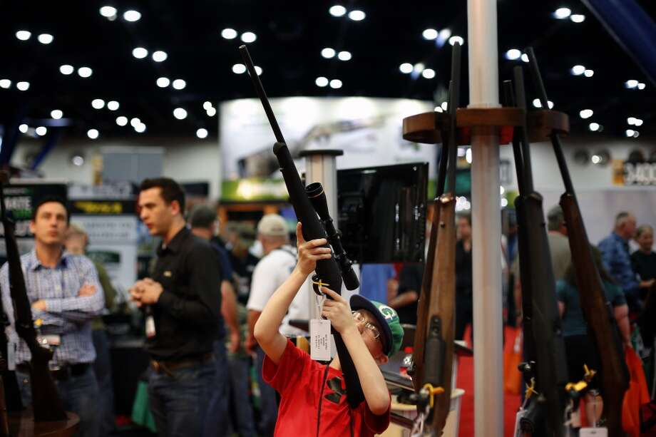 11-year-old Ryan Weaver inspects a rifle, during day 2 of the 142nd NRA annual meetings and exhibits, Saturday, May 4, 2013 at the George R Brown convention center in Houston, Texas. (TODD SPOTH FOR THE CHRONICLE) Photo: © TODD SPOTH, 2013
