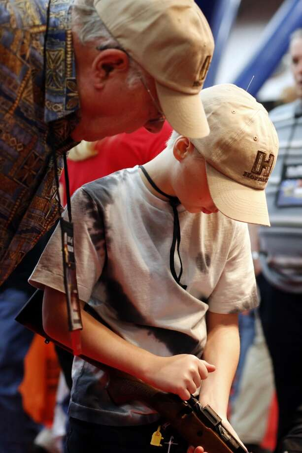 10-year-old Bryce Danforth of St. Augustine, Florida inspects a rifle while his grandfather watches closely, during day 2 of the 142nd NRA annual meetings and exhibits, Saturday, May 4, 2013 at the George R Brown convention center in Houston, Texas. (TODD SPOTH FOR THE CHRONICLE) Photo: © TODD SPOTH, 2013