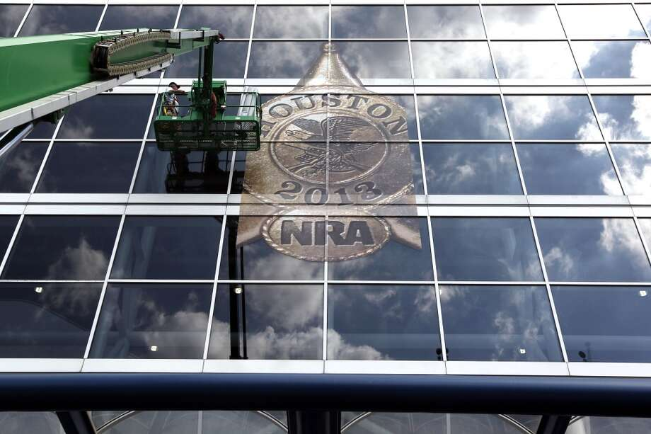 The National Rifle Association's 142 Annual Meetings and Exhibits logo is placed on the George R. Brown Convention Center by Lynn Creel, left, and Don Reynolds with Display Graphics Wednesday, May 1, 2013, in Houston.  The 2013 NRA Annual Meetings and Exhibits runs from Friday, May 3, through Sunday, May 5.  More than 70,000 are expected to attend the event with more than 500 exhibitors represented. The convention will features training and education demos, the Antiques Guns and Gold Showcase, book signings, speakers including Glenn Beck, Ted Nugent and Sarah Palin as well as NRA Youth Day on Sunday ( Johnny Hanson / Houston Chronicle ) Photo: Houston Chronicle