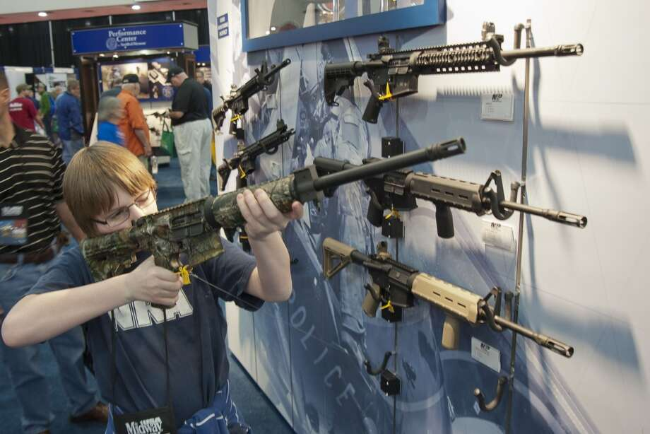 A young man who chose not to give his name sizes-up an assault style rifle during the National Rifle Association's annual convention Friday, May 3, 2013 in Houston. (AP Photo/Steve Ueckert) Photo: Associated Press