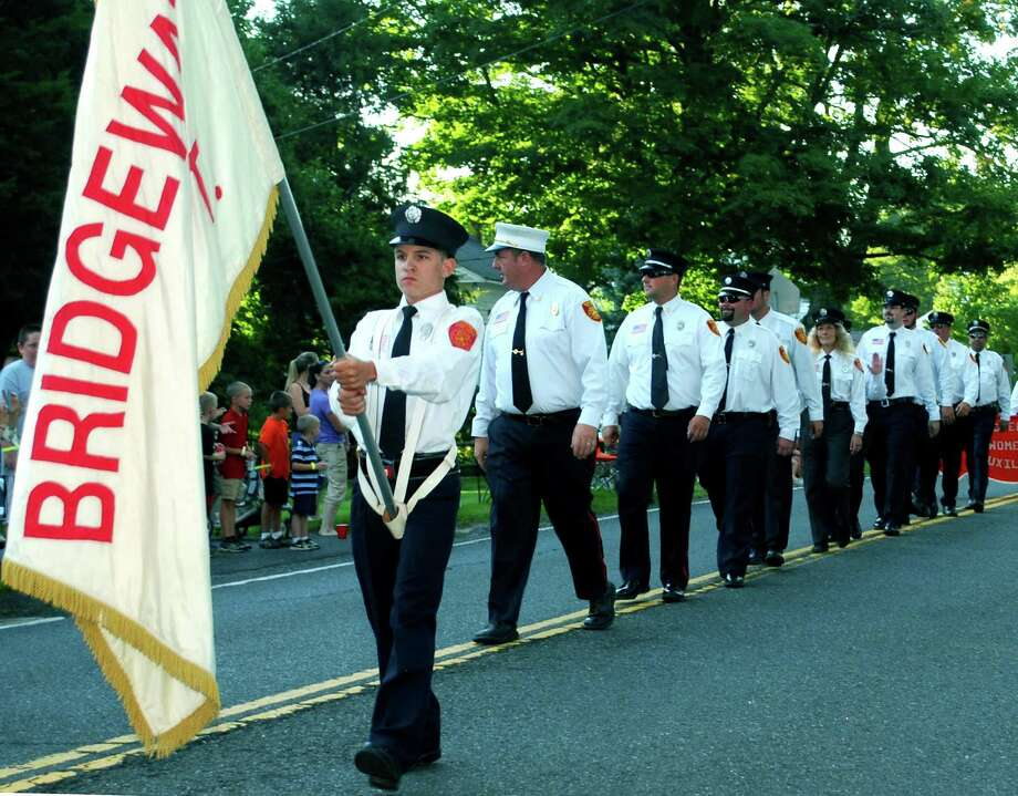 Junior fireman Jacob Marsh bears the firefighters' flag as he leads fellow of the Bridgewater Volunteer Fire Department along the Route 133 parade route to kick off the Bridgewater Country Fair. Jacob is followed by Chief Eric Gsell, Captain Joshua Murphy, first lieutenant Pat Hearn, Matt Conway, Cindy Bennett, Ryan Underwood, Conner Dillon, Scott Shail and Brian Sullivan. Aug. 16, 2013. Photo: Deborah Rose