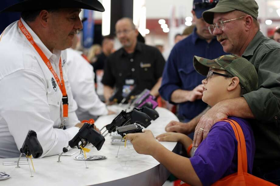 A father and son browse pistols, during day 2 of the 142nd NRA annual meetings and exhibits, Saturday, May 4, 2013 at the George R Brown convention center in Houston, Texas. (TODD SPOTH FOR THE CHRONICLE) Photo: © TODD SPOTH, 2013