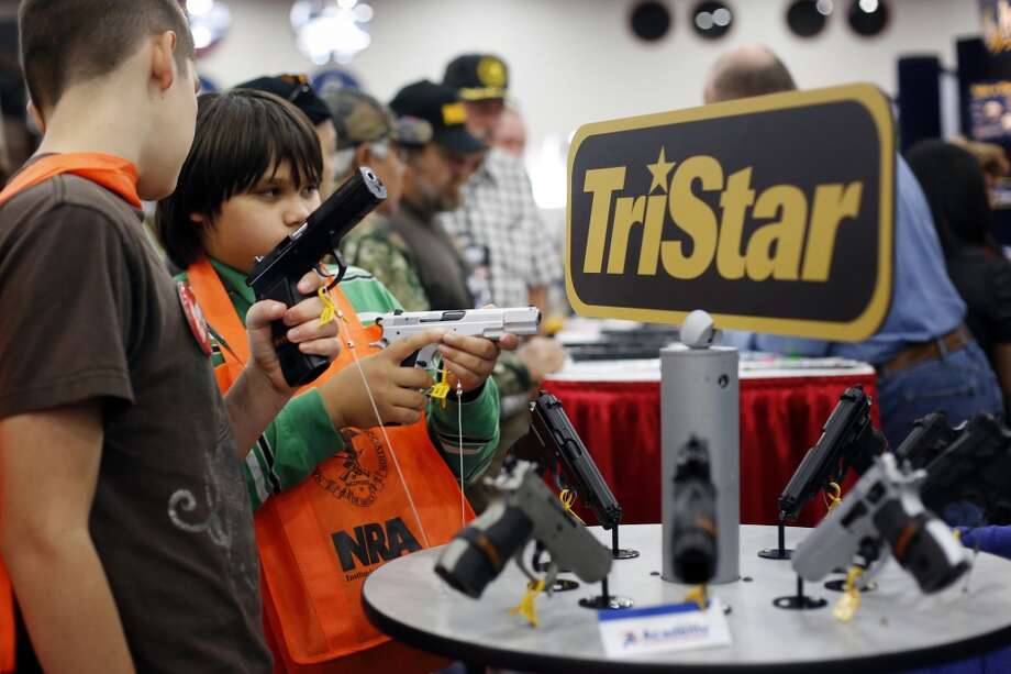Brothers, 10-year-old Kayden La, middle, and 13-year-old Jacob La, left, inspect pistols at a booth, during day 2 of the 142nd NRA annual meetings and exhibits, Saturday, May 4, 2013 at the George R Brown convention center in Houston, Texas. (TODD SPOTH FOR THE CHRONICLE) Photo: © TODD SPOTH, 2013
