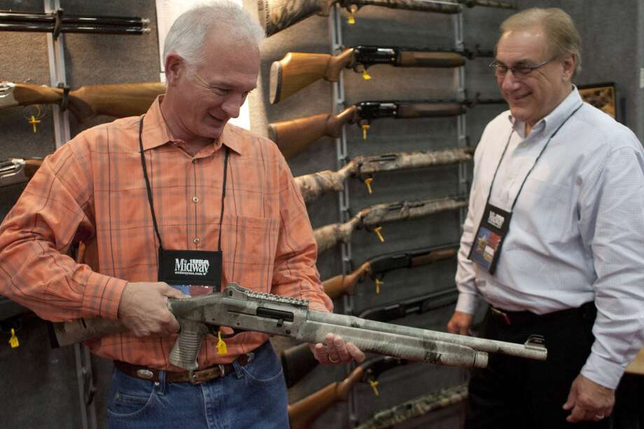 New NRA members Joey Sullivan, of Montgomery, left, and Tim Armand of Houston, right, look at firearms in the exhibit hall at the National Rifle Association's 142 Annual Meetings and Exhibits in the George R. Brown Convention Center Friday, May 3, 2013, in Houston.  The 2013 NRA Annual Meetings and Exhibits runs from Friday, May 3, through Sunday, May 5.  More than 70,000 are expected to attend the event with more than 500 exhibitors represented. The convention will features training and education demos, the Antiques Guns and Gold Showcase, book signings, speakers including Glenn Beck, Ted Nugent and Sarah Palin as well as NRA Youth Day on Sunday ( Johnny Hanson / Houston Chronicle ) Photo: Houston Chronicle