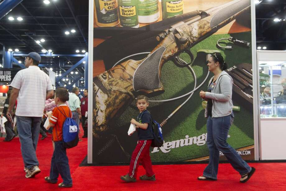 From right, Heath Bryant, of Cypress, and his family Fisher, 6, Tate, 5, and wife Rebecca, walk through the exhibit hall during NRA Youth Day events at the National Rifle Association's 142 Annual Meetings and Exhibits in the George R. Brown Convention Center Sunday, May 5, 2013, in Houston.  More than 70,000 are expected to attend the event with more than 500 exhibitors represented. ( Johnny Hanson / Houston Chronicle ) Photo: Houston Chronicle