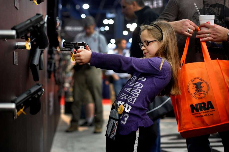 7-year-old Sydney Morgan inspects a Sig Sauer pistol, during day 1 of the 142nd NRA annual meetings and exhibits, Friday, May 3, 2013 at the George R Brown convention center in  (TODD SPOTH FOR THE CHRONICLE) Photo: © TODD SPOTH, 2013