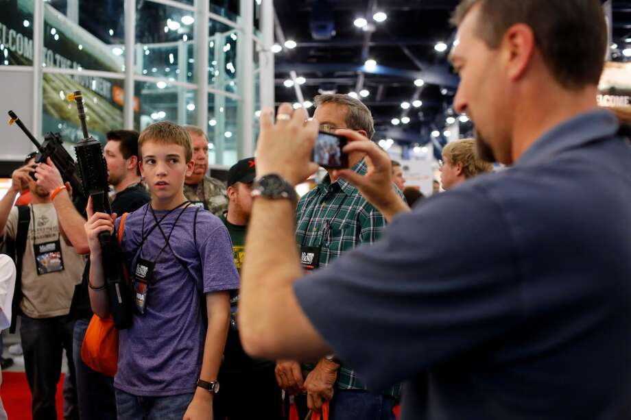 14-year-old Caleb Lofton, middle poses with a rifle while his father, James, right, takes a photo, during day 2 of the 142nd NRA annual meetings and exhibits, Saturday, May 4, 2013 at the George R Brown convention center in Houston, Texas. (TODD SPOTH FOR THE CHRONICLE) Photo: © TODD SPOTH, 2013