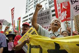 Anti-Japan protesters demonstrate against what they say is a growing Japanese aggression on fishing waters in East China Sea near a group of Japanese-controlled disputed islands called Senkaku by Japan and Diaoyu by China, also claimed by China and Taiwan, outside the Japanese trade office in Taipei, Taiwan, Thursday, Aug. 15, 2013. The protest was to mark the 68th anniversary of Japan's surrender in World War II. (AP Photo/Wally Santana)