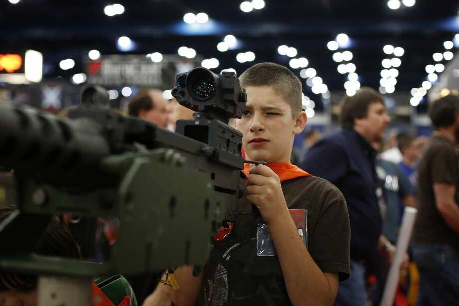 13-year-old Jacob La looks down the sight of a mounted machine gun, during day 2 of the 142nd NRA annual meetings and exhibits, Saturday, May 4, 2013 at the George R Brown convention center in Houston, Texas. (TODD SPOTH FOR THE CHRONICLE) Photo: © TODD SPOTH, 2013