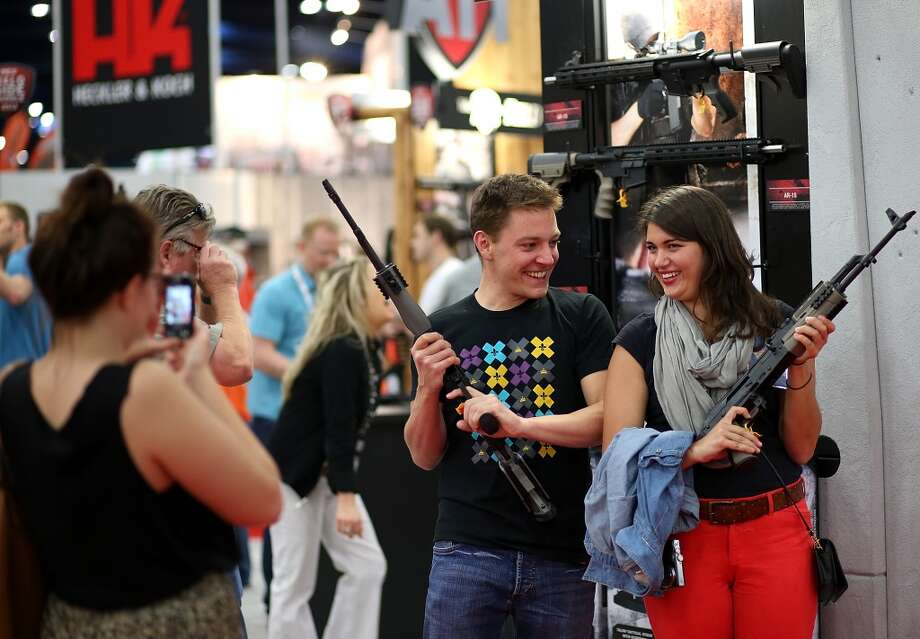 Attendees hold assault rifles as they pose for a photo during the 2013 NRA Annual Meeting and Exhibits at the George R. Brown Convention Center on May 4, 2013 in Houston, Texas.  More than 70,000 people are expected to attend the NRA's 3-day annual meeting that features nearly 550 exhibitors, gun trade show and a political rally. The Show runs from May 3-5.  (Photo by Justin Sullivan/Getty Images) *** BESTPIX *** Photo: Justin Sullivan, Getty Images