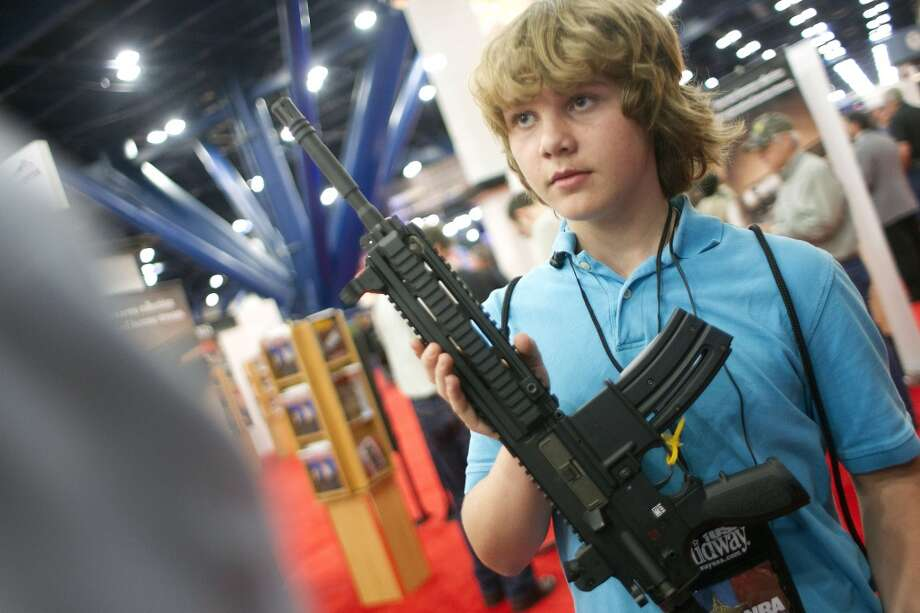 James Beaver, 13, of Denison, holds an HK 416 D at the NRA Whittington Center Outdoor Adventure exhibit booth at the National Rifle Association's 142 Annual Meetings and Exhibits in the George R. Brown Convention Center Friday, May 3, 2013, in Houston.  The 2013 NRA Annual Meetings and Exhibits runs from Friday, May 3, through Sunday, May 5.  More than 70,000 are expected to attend the event with more than 500 exhibitors represented. The convention will features training and education demos, the Antiques Guns and Gold Showcase, book signings, speakers including Glenn Beck, Ted Nugent and Sarah Palin as well as NRA Youth Day on Sunday ( Johnny Hanson / Houston Chronicle ) Photo: Houston Chronicle
