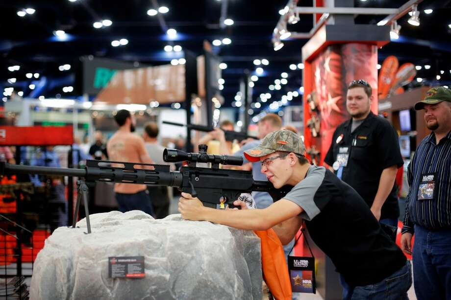 Grant Siebrecht of Needville inspects a rifle, during day 2 of the 142nd NRA annual meetings and exhibits, Saturday, May 4, 2013 at the George R Brown convention center in Houston, Texas. (TODD SPOTH FOR THE CHRONICLE) Photo: © TODD SPOTH, 2013