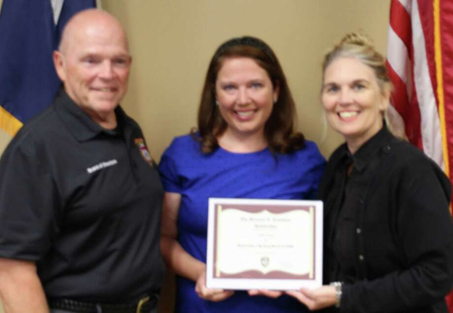 Steve Stevenson, vice chairman of the Bulverde-Spring Branch EMS board (left) and EMS Chief Executive Director Mechelle Salmon (right) present Ashley Hoppe with the Livaudais EMS Scholarship on Monday. Photo: Courtesy Photo