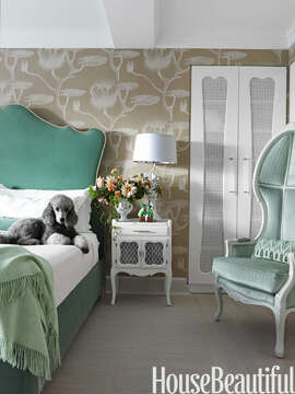 "Fantastical Bedroom   Lolly, the family poodle, lounges in the Dorothy Draper-influenced master bedroom. Galli chose the overscale  Cole & Son  wallpaper, Lily, for ""the fairy-tale feeling."" The lily pads and the Old World Weavers green velvet, Languedoc, on the headboard evoke the romance of a garden pond. The French Canopy chair from  Artistic Frame  is covered in  Beacon Hill 's In Between."