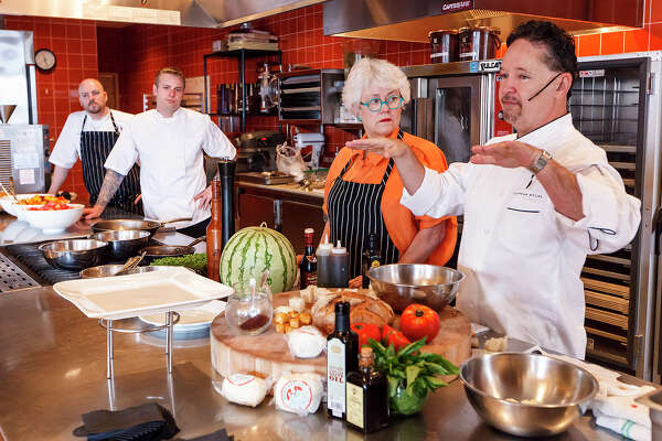 """Celebrity Chef Stephan Pyles (from right) and Paula Lambert, founder of Dallas' Mozzarella Company, prepare a Tomato, Watermelon and Mozzarella Salad for an audience during a cooking demonstration at Sustenio at The Éilan Hotel & Spa during """"Ripe: A Spirited Market at Éilan"""" on Sunday, July 21, 2013. Twenty-seven vendors including food trucks participated in the event. The market will run monthly through August and weekly on Sundays starting September 8. MARVIN PFEIFFER/ mpfeiffer@express-news.net"""