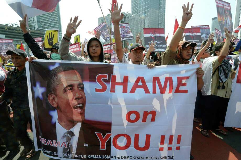 Indonesian Muslim demonstrators shout slogans and hold a banner of U.S. President Barack Obama during a rally to show their support for the Egyptian people and ousted president Mohamed Morsi. A reader criticizes Obama for condemning the violence in Egypt while not completely cutting off aid to the government perpetrating that violence. Photo: Adek Berry / Getty Images