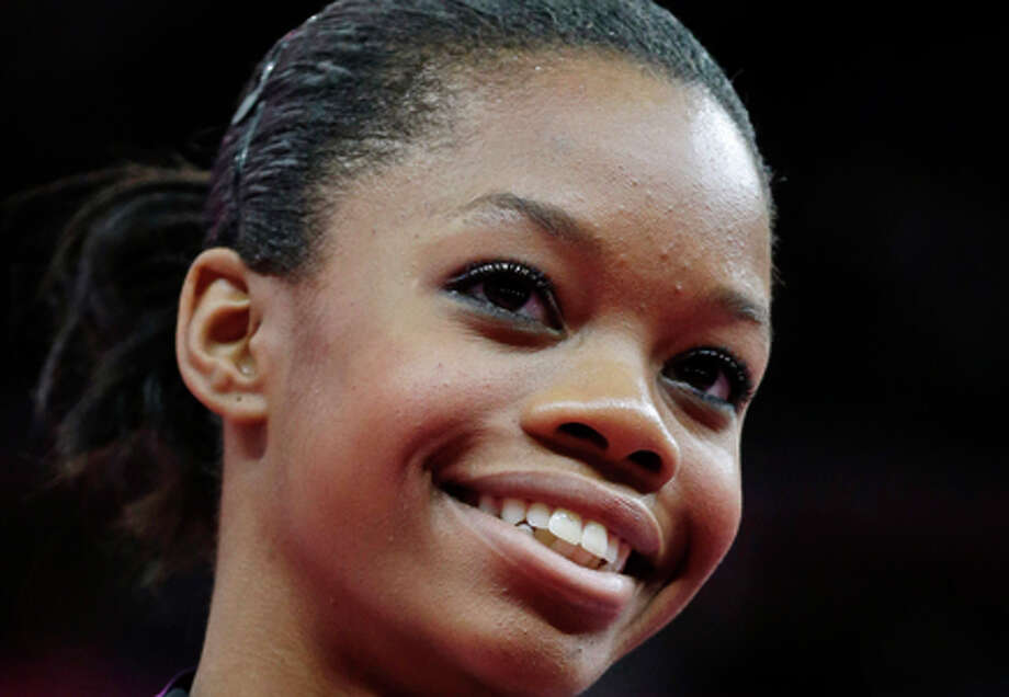 In this Aug. 2, 2012, file photo, Gabrielle Douglas of the United States displays her gold medal in the artistic gymnastics women's individual all-around competition at the 2012 Summer Olympics in London. Douglas, who became the first African-American gymnast to win the all-around Olympic title, is The Associated Press' 2012 female athlete of the year. (AP Photo/Julie Jacobson, File) Photo: Julie Jacobson / Associated Press / AP