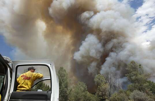 A firefighter watches along Ferretti Rd. in Groveland, Calif., as the 16,000 acre Rim Fire continues to grow on Wednesday August 21, 2013. Photo: Michael Macor, San Francisco Chronicle
