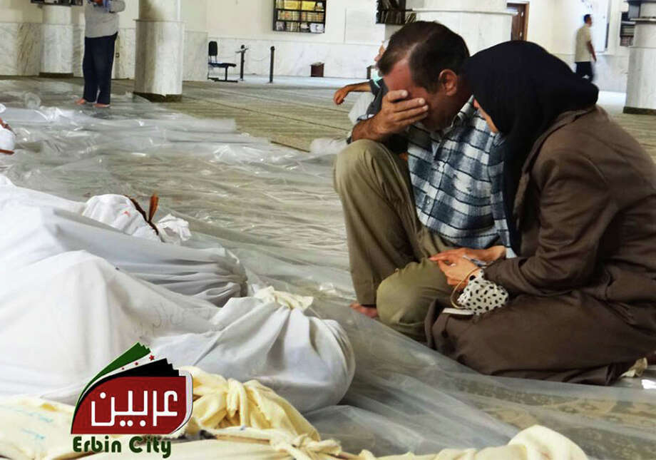 In this photo provided by the Local Committee of Arbeen, which has been authenticated based on its contents and other AP reporting, a man and woman mourn over the dead bodies of Syrian men after an alleged poisonous gas attack fired by regime forces, according to activists in Arbeen town on Wednesday. Photo: HOEP / Local Committee of Arbeen