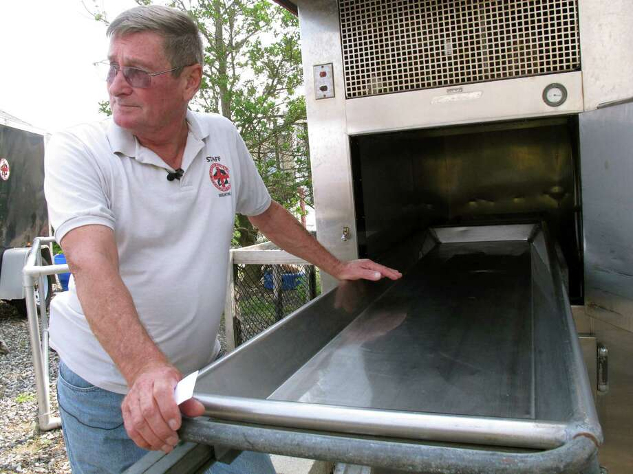 Bob Schoelkopf, co-director of the Marine Mammal Stranding Center, checks a refrigerated unit used to preserve dead dolphins that the center retrieves. Photo: Wayne Parry, STF / AP