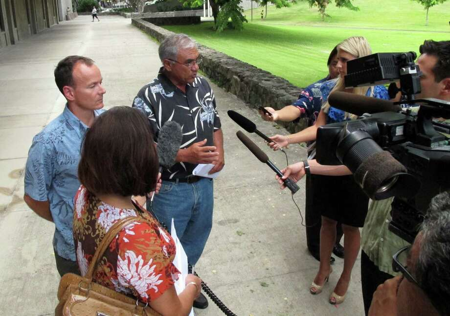 Chairman William Aila of the Hawaii Department of Land and Natural Resources, center, speaks to reporters at a news conference in Honolulu on Tuesday, Aug. 20, 2013. Hawaii officials plan to spend the next two years studying tiger shark movements around Maui amid what they call an unprecedented spike in overall shark attacks since the start of 2012. Photo: Oskar Garcia