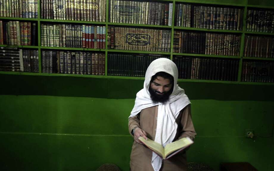 A Pakistani student looks at a religious book in the Ganj Madrassa on Wednesday. The U.S. claims the school is a terrorist training center. Photo: Mohammad Sajjad, STR / AP