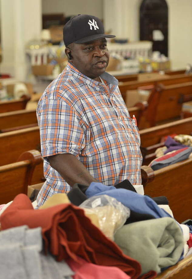 Pastor Willie Bacote stands in the sanctuary of the Missing Link AME Zion Church May 24, 2013, amidst the products to be given away to residents of public housing in Troy, N.Y. (Skip Dickstein/Times Union)