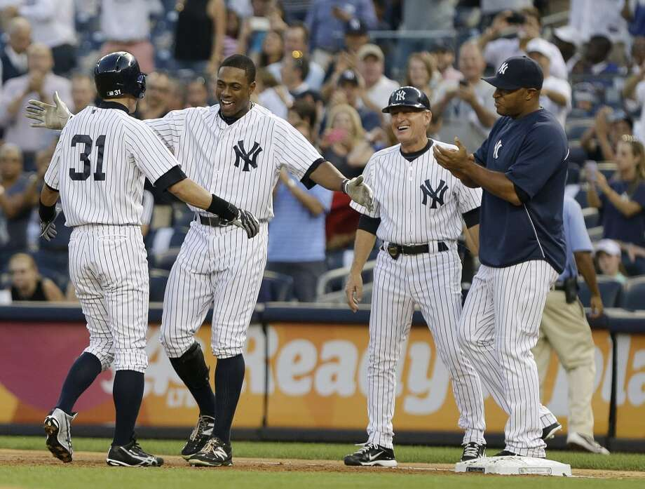 Ichiro Suzuki, left, is congratulated by -- from left to right -- Curtis Granderson, coach Mike Kelleher and Vernon Wells, all of the New York Yankees, after Suzuki recorded his 4,000th hit Wednesday at Yankee Stadium. Photo: Frank Franklin II, Associated Press