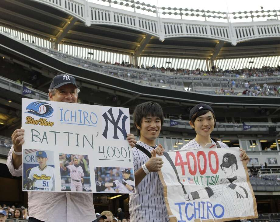 Yankees fans hold up signs in honor of Ichiro Suzuki at the start of Wednesday's game between New York and Toronto at Yankee stadium. Suzuki recorded his 4,000th hit in his first at-bat in the first inning. Photo: Kathy Willens, Associated Press