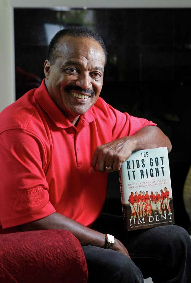 "Jerry LeVias poses with the new book in which he is featured titled ""The Kids Got It Right: How the Texas All-Stars Kicked Down Racial Walls"" by Jim Dent shown Wednesday, Aug. 21, 2013, in Houston.  LeVias, a former NFL player, helped break the color barrier in football in the state of Texas. Photo: Melissa Phillip, Houston Chronicle / © 2013  Houston Chronicle"