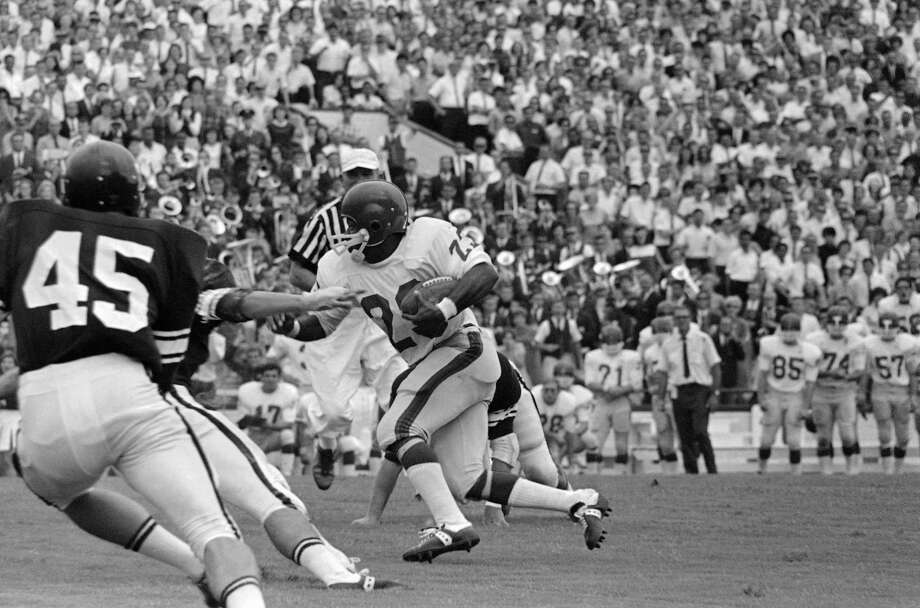 Southern Methodist University's halfback, Jerry Levias (23) carries the ball for an 8 yard gain against Texas A & M at College Station, Tex. on Saturday, Sept. 16, 1967. Levias evaded one unidentified A & M tackler while another, Grady Allen (89), an Aggie end, trials along behind the play. The loss of Levias' shoe doesn't seem to slow him a bit. This was second quarter action. Photo: FK, ASSOCIATED PRESS / AP1967