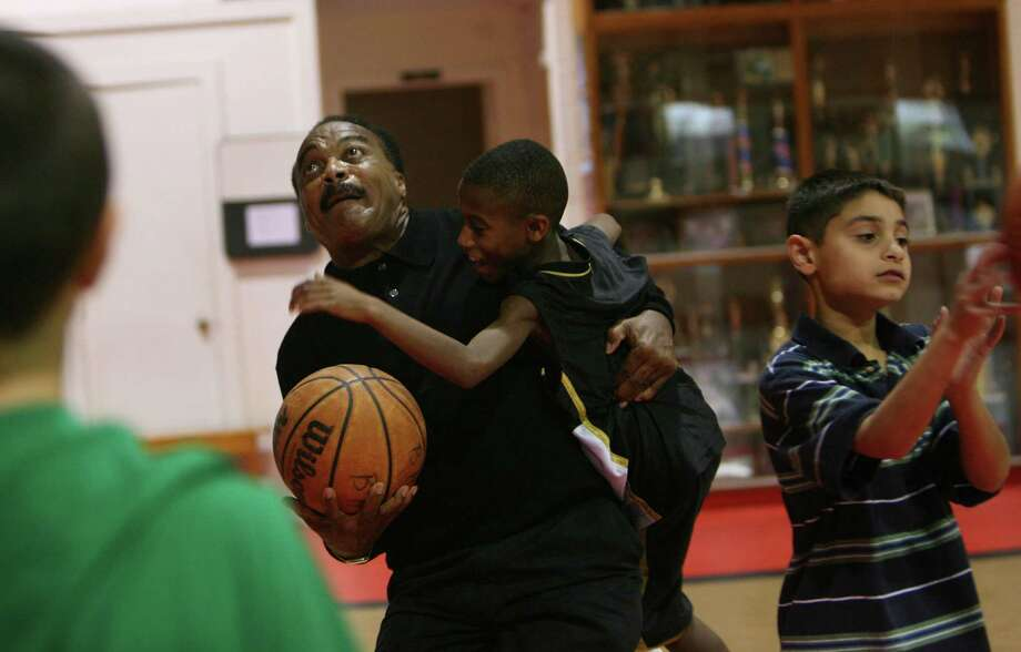 Jerry LeVias, Boys & Girls Harbor Outreach Director, carries Marcus  Collins, 12, after stealing the basketball from him during the students break in the gym at Boys & Girls Harbor on Tuesday, Dec. 9, 2008, in La Porte. Photo: Mayra Beltran, Houston Chronicle / Houston Chronicle