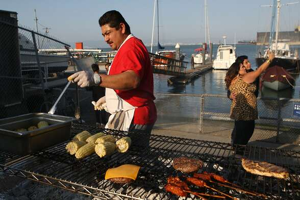 Jose Guzman watches the barbecue at the Ramp in San Francisco, Calif., as a couple takes pictures in the background on Saturday, July 20, 2013.