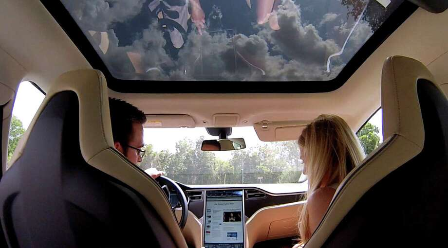 Express-News business reporter Neal Morton, left, and Tesla Motors communications team member Alexis Georgeson sits in an all-electric Tesla Model S sedan on Wednesday, Aug. 21, 2013. Photo: Billy Calzada, San Antonio Express-News / San Antonio Express-News