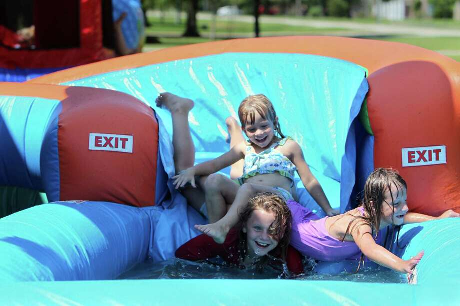 The Burwell sisters - Evangeline, top, Catalana and Elizabeth, right - enjoy their mother's inflatables business in Baytown. Photo: Mayra Beltran, Staff / © 2013 Houston Chronicle