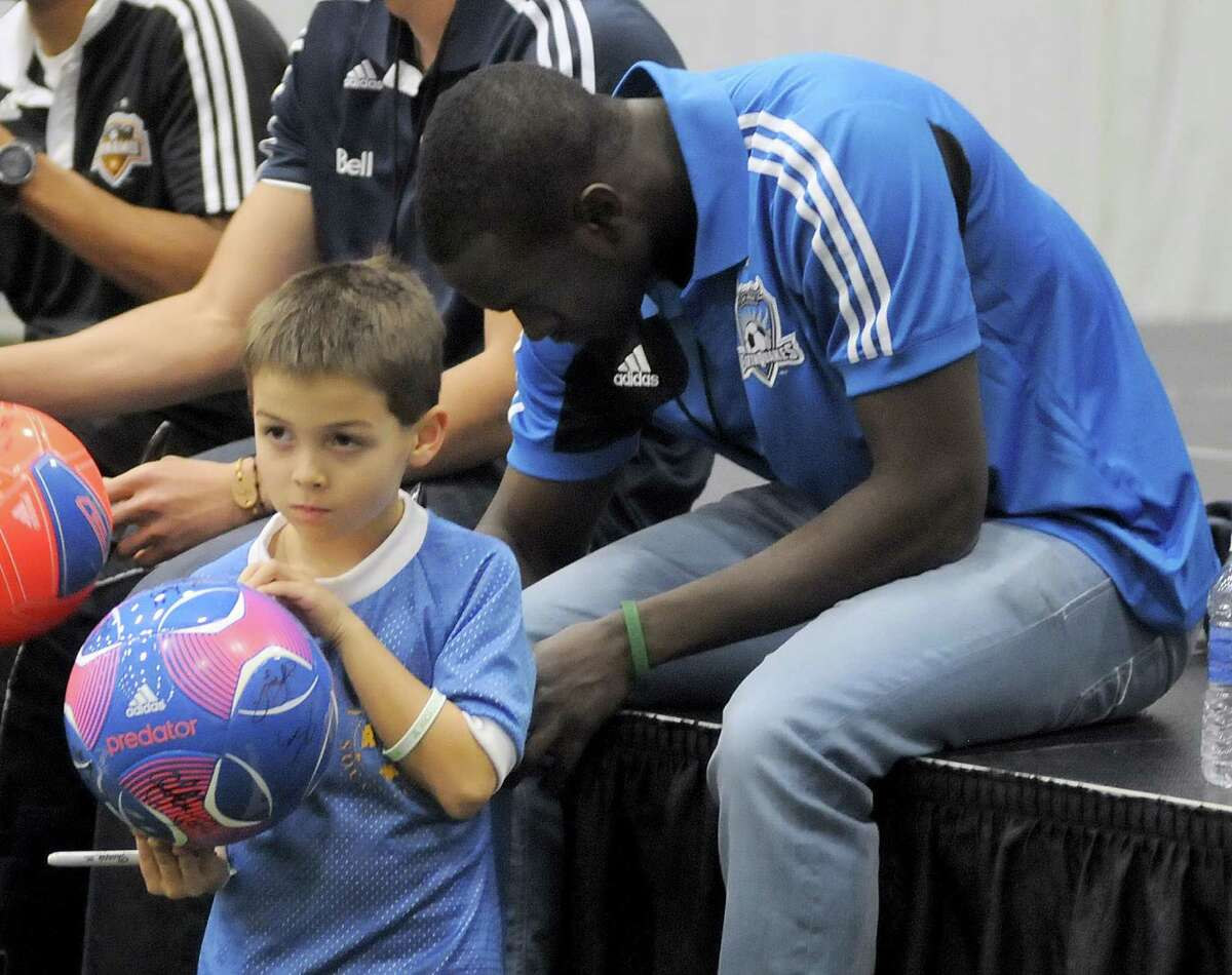 Sandy Hook first grader Ryan Zaniewski, 6, gets his jersey signed by American soccer player, Marcus Tracy, also of Newtown, during the Soccer Night in Newtown on Monday Jan. 7, 2013.